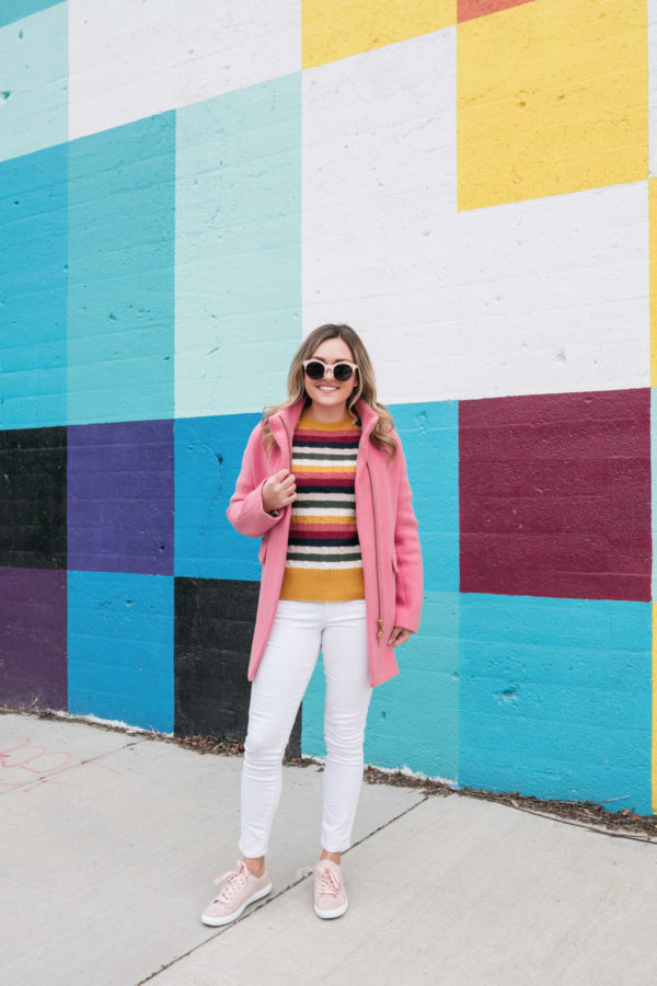 Chicago influencer Jessica Sturdy of Bows & Sequins wears white jeans in the winter with a pink coat and sneakers.