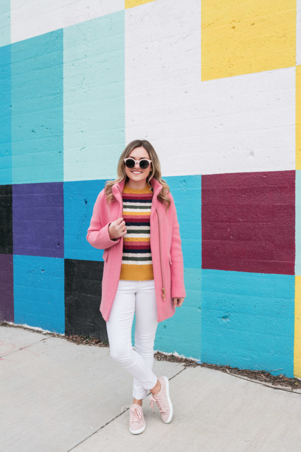 Chicago lifestyle influencer and blogger Jessica Sturdy of Bows & Sequins styling winter white jeans with a hot pink coat and sneakers.