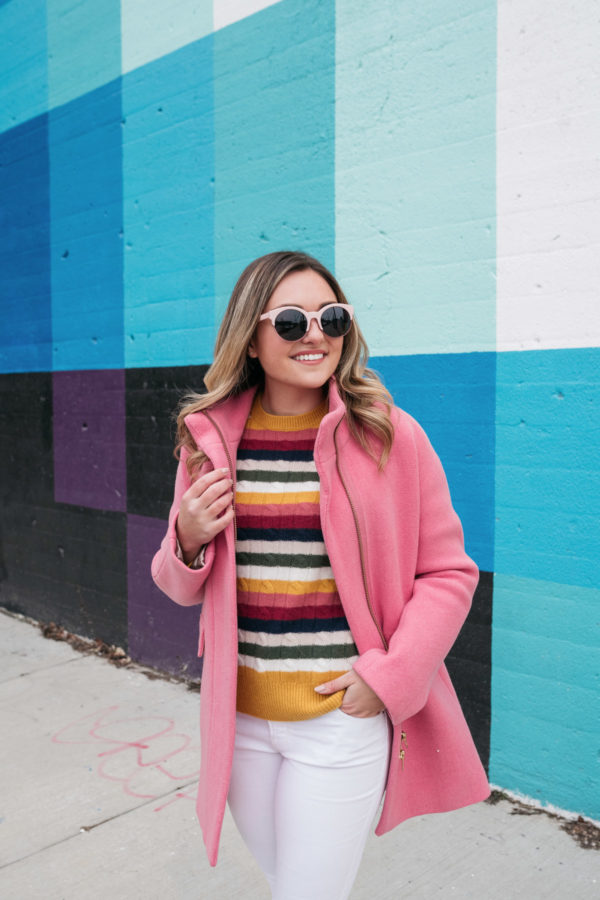 Chicago style blogger Bows & Sequins wearing a bright pink coat and a colorful striped cashmere sweater.