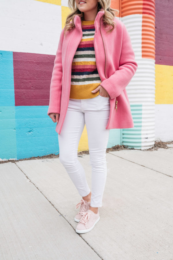 Fashion blogger styles white jeans in the winter with pink sneakers, a bright pink coat, and a colorful sweater.