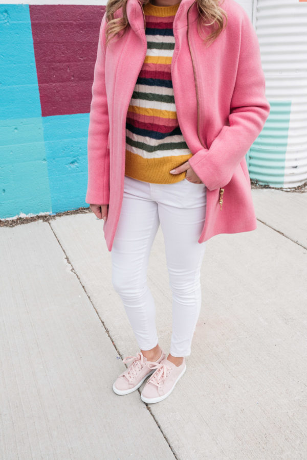 Blogger styles outfit with white jeans and blush pink tennis shoes with a striped sweater and a hot pink J.Crew coat.