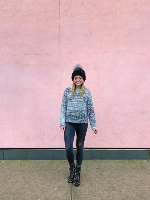 Bows & Sequins wearing a Bobeau sweater, rag & bone legging jeans, combat boots, and a fur beanie in front of a pink wall in Lincoln Park.