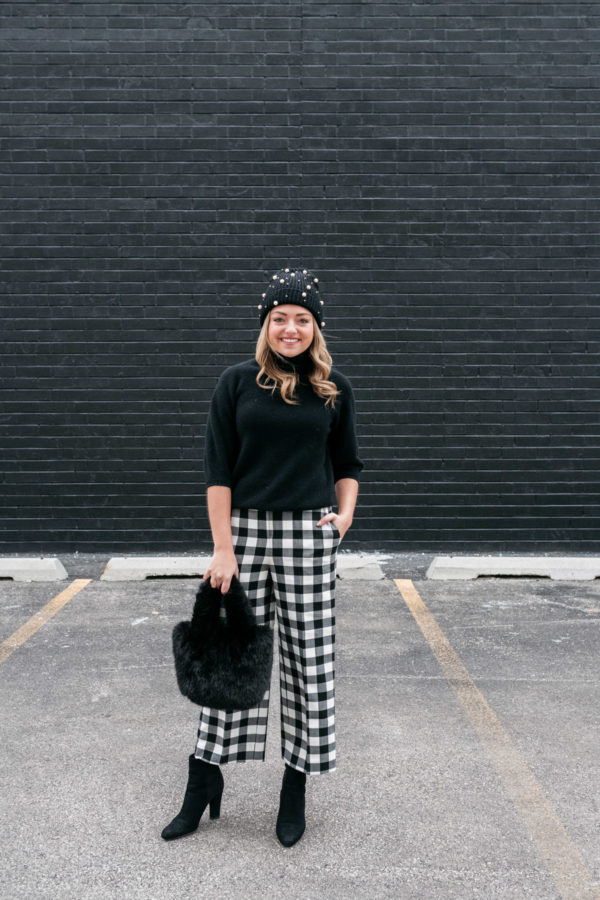 Chicago wardrobe stylist Jessica Sturdy wearing a black turtleneck with gingham pants, a faux fur handbag, and a pearl beanie.