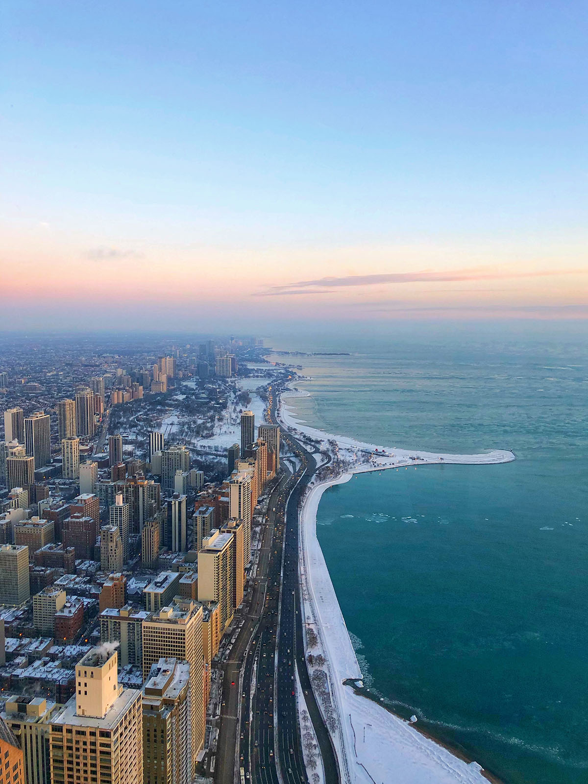 View from the Hancock Building's 360 Observatory on the 94th floor in Chicago. This is looking north at the lake and the Gold Coast, Old Town, and Lincoln Park at sunrise!