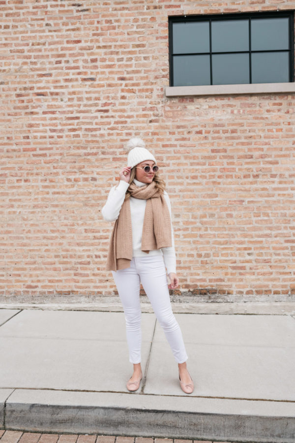 Lifestyle blogger Bows & Sequins styling a monochromatic white winter outfit with a pom-pom beanie and a scarf.