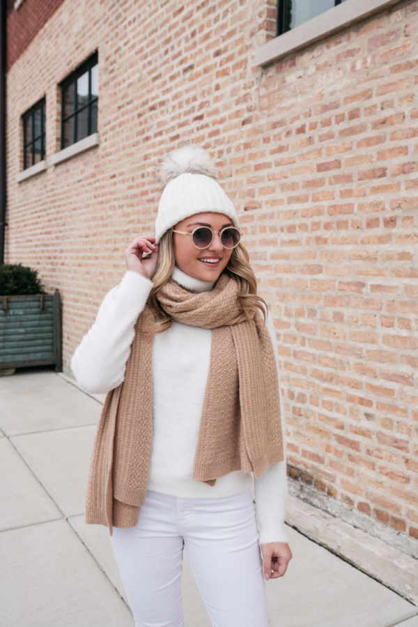 Top Chicago lifestyle influencer Jessica Sturdy wearing a cashmere blanket scarf, round sunglasses, and a fur pom-pom hat.