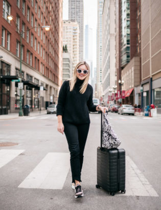 Bows & Sequins styling an all black travel outfit with a MZ Wallace printed tote and an Away Bigger Carry-On.