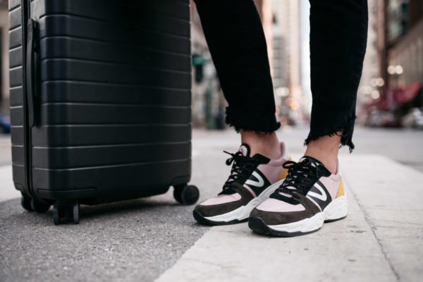 Bows & Sequins wearing Tretorn Lexie3 dad sneakers for a comfortable travel outfit with an Away suitcase.