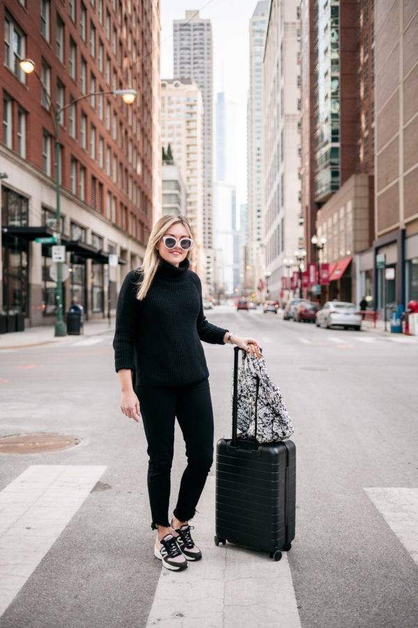Bows & Sequins styling an all-black travel day outfit: 525 America Cotton Turtleneck, Paige black skinny jeans, Tretorn dad sneakers, MZ Wallace Small Metro Tote in Black & White Paint Splatter, and a monogrammed black suitcase from Away.
