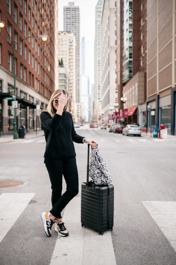 Bows & Sequins wearing a 525 America turtleneck sweater, Paige Hoxton raw-hem skinny jeans, Tretorn Lexie 3 sneakers, MX Wallace Metro Tote, and a black Away luggage.