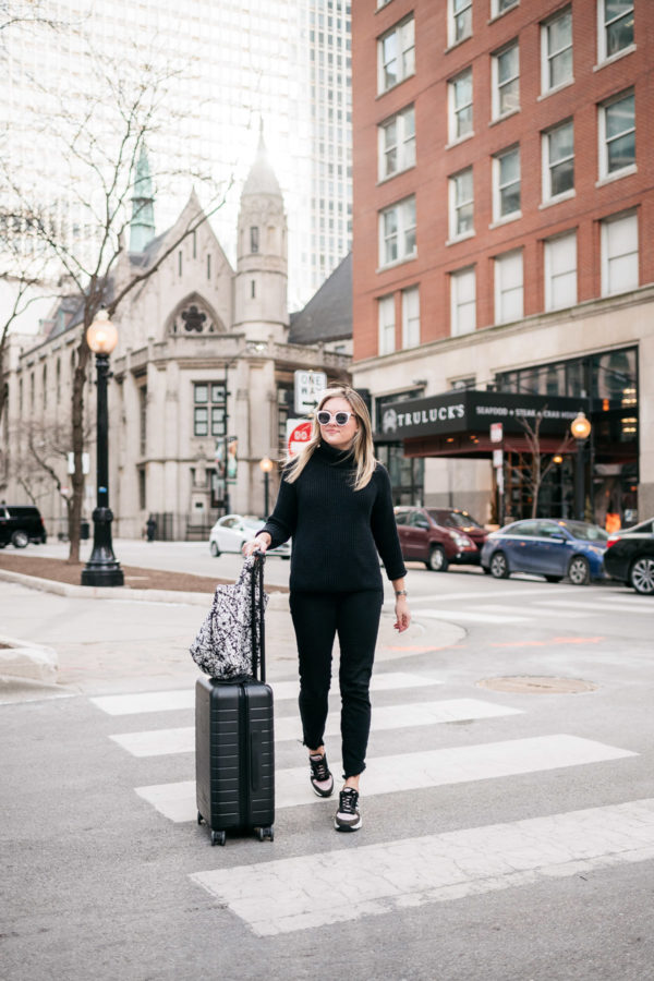Chicago travel influencer Jessica Sturdy of Bows & Sequins wearing an all black outfit to the airport.