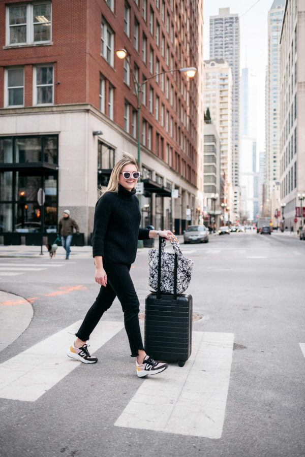 Chicago travel blogger Jessica Sturdy of Bows & Sequins showing her travel day style with fun sneakers, a black Away Bigger Carry-On suitcase, and a black and white printed MZ Wallace Metro Tote.