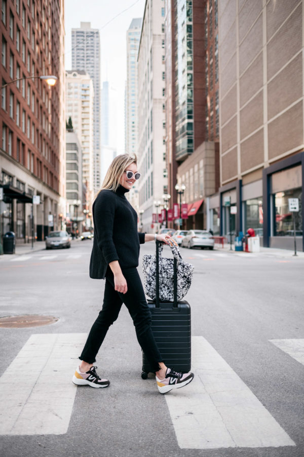 Bows & Sequins sharing an all-black outfit for a travel day with an Away suitcase, colorful sneakers, and a MZ Wallace Metro Tote.