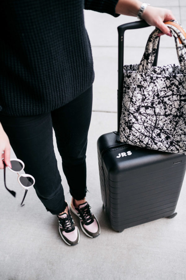 Jessica Sturdy wearing black jeans, colorful sneakers, a paint splattered MZ Wallace Metro Tote, and a monogrammed Away Suitcase.