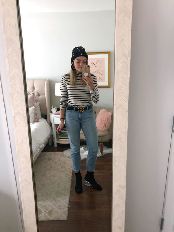 Bows & Sequins wearing a pearl beanie, striped turtleneck, Gucci belt, light wash mom jeans, and lucite heel booties.