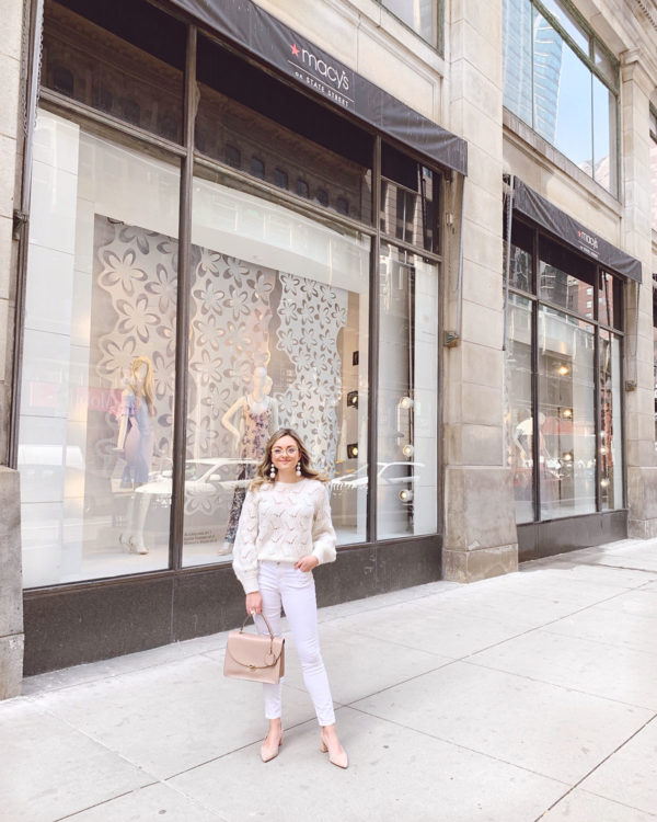 Chicago personal stylist Jessica Sturdy wearing a cream pointelle sweater with white jeans, a blush leather structured tote, nude suede slingbacks, and goldrim glasses.