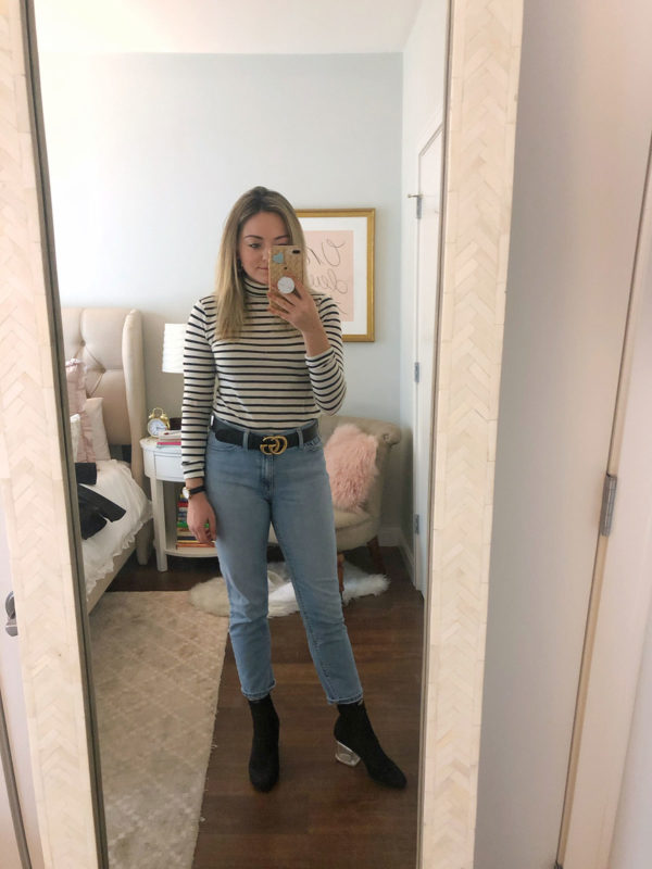 Bows & Sequins wearing a black and white striped turtleneck tee, Mott & Bow mom jeans, and a Gucci belt with sock booties with a clear heel.