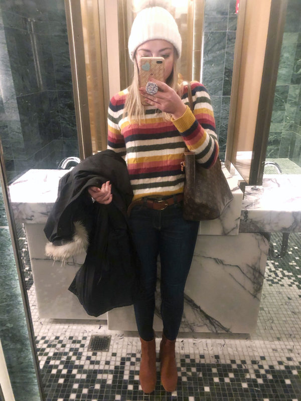 Bows & Sequins wearing a colorful striped sweater with skinny jeans, cognac ankle booties, and a pom-pom hat.