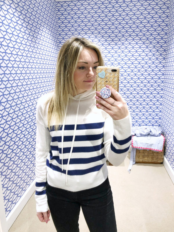 Bows & Sequins trying on a striped hoodie at Vineyard Vines