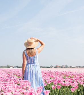 Lifestyle influencer Jessica Sturdy wearing a blue and white striped dress with a straw boater hat in a pink tulip field with blue skies in Amsterdam.