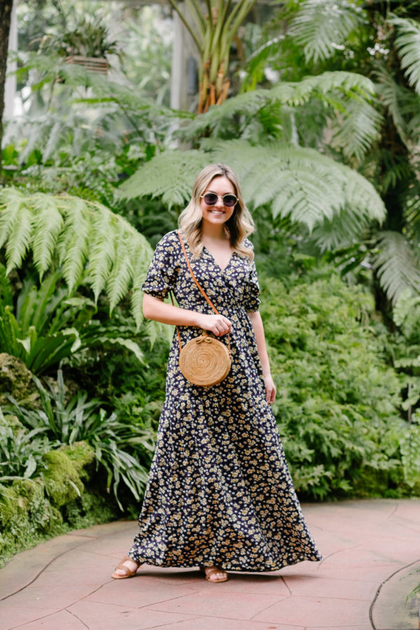Fashion blogger in Chicago Jessica Sturdy of Bows & Sequins styles a floral maxi dress with a round rattan bag for an easy summer outfit.