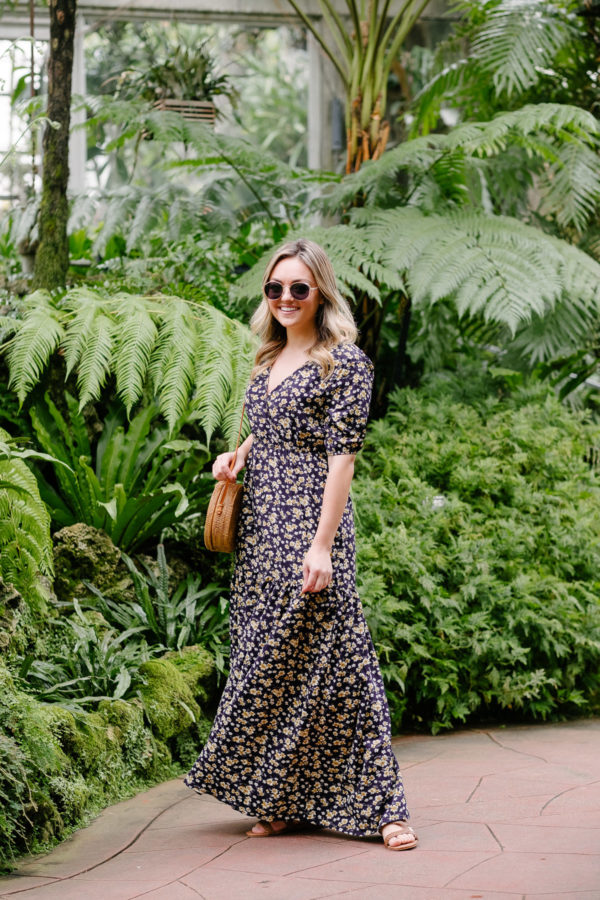 Women's fashion blogger Bows & Sequins shares a summer outfit idea. She is wearing a v-neck floral maxi dress with puff sleeves.
