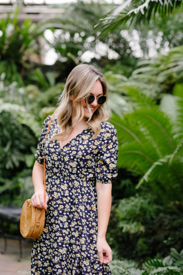 Fashion blogger Jessica Sturdy styles a floral maxi dress with a round rattan bag and small sunglasses for summer outfit ideas on Pinterest.