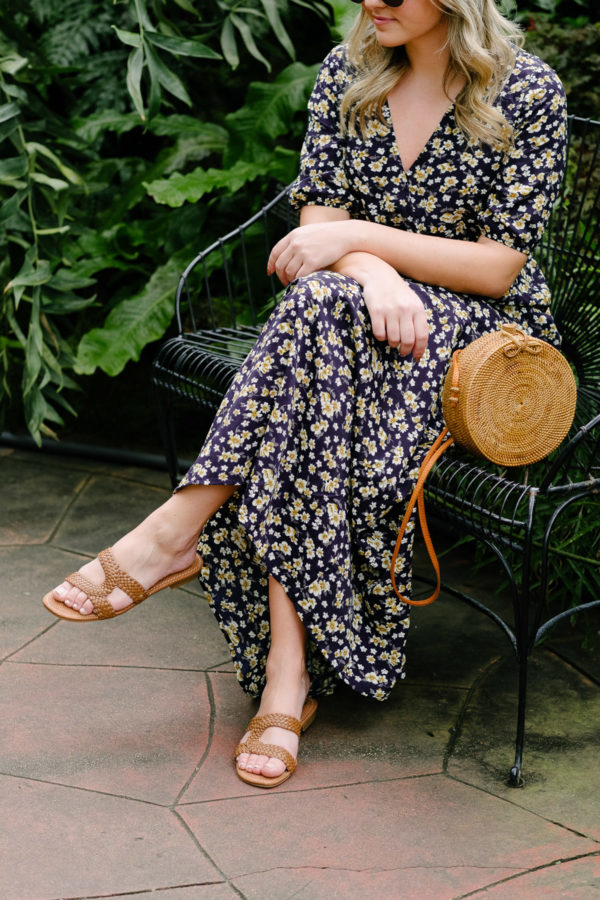 Travel and lifestyle blogger Bows & Sequins wearing a floral maxi dress, a round rattan bag, and Sam Edelman Circus sandals.