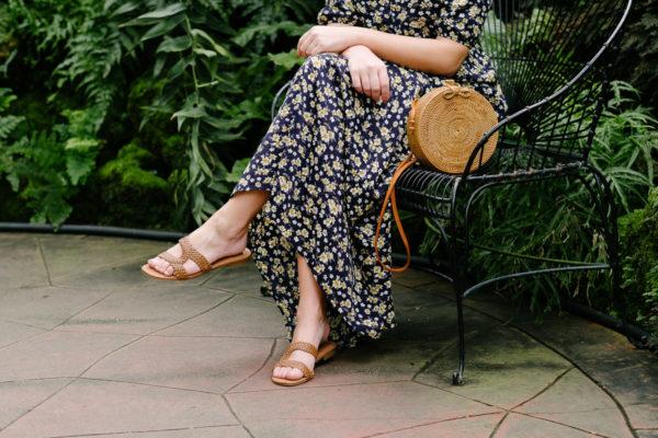 Fashion and travel blogger Bows & Sequins styling a floral maxi dress with leather sandals and a Bali rattan bag.