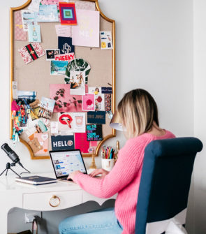 Bows & Sequins sitting at her Bungalow 5 desk in Chicago with a gold memo board and a gold Macbook.