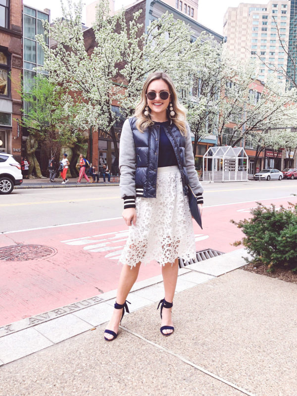 Fashion and beauty lifestyle influencer Jessica Sturdy of Bows & Sequins styling a Veronica Beard puffer jacket with a lace midi skirt and Boden ankle strap heels for a sporty and cute spring outfit.