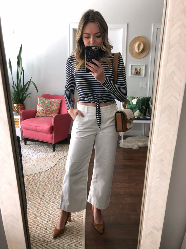 Lifestyle blogger Jessica Sturdy of Bows & Sequins wearing a striped crop top with white wide leg pants, pointed pumps, and a Michael Kors bag.
