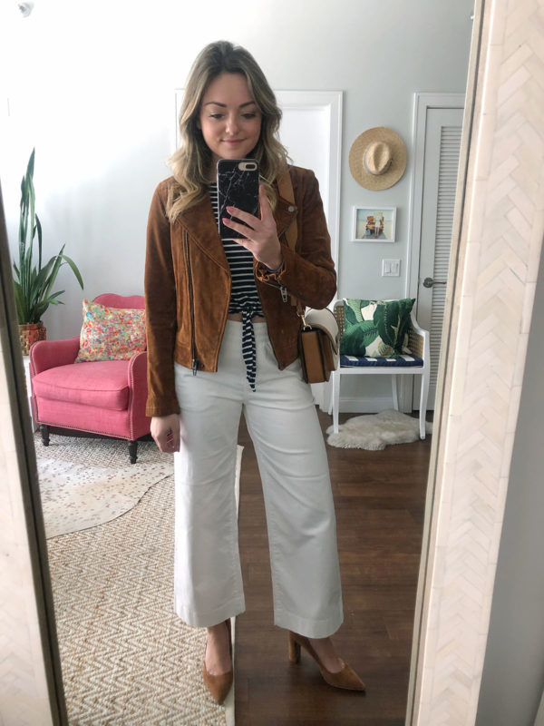 Fashion blogger Jessica Sturdy of Bows & Sequins wearing white wide leg pants with a cognac suede moto jacket.