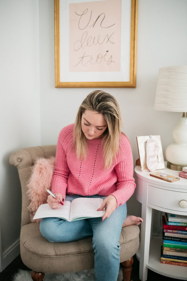 Chicago lifestyle and wellness blogger Bows & Sequins writing in a journal in her bedroom.