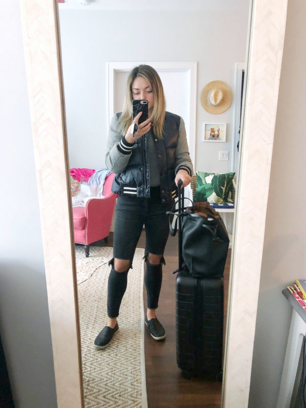 Travel blogger wearing a Veronica Beard jacket, ripped One Teaspoon jeans, and Joie sneakers with the Away Bigger Carry-On suitcase.