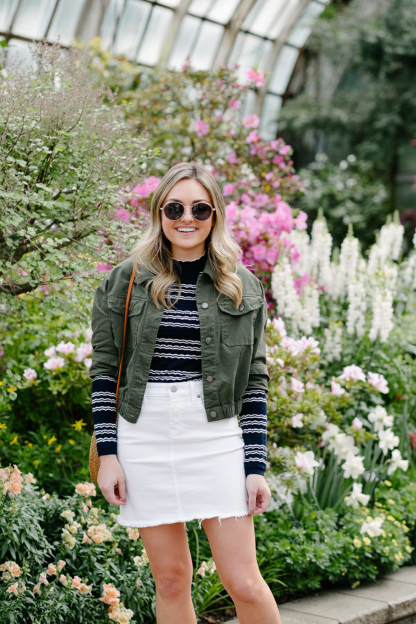 Chicago blogger Jessica Sturdy of Bows & Sequins wearing a white denim skirt at the conservatory gardens in Lincoln Park.