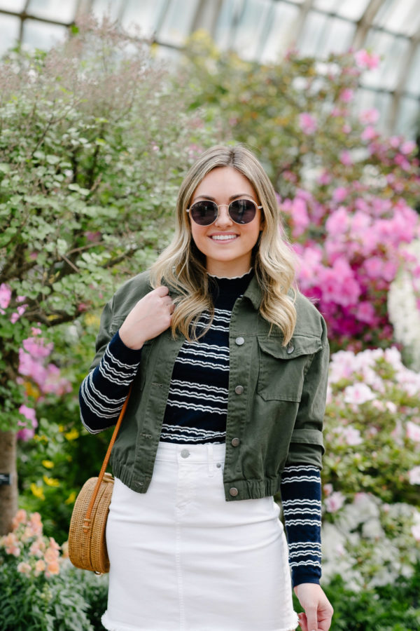 Chicago fashion and beauty blogger Bows & Sequins styling a cropped green anorak jacket with white denim, round sunglasses, and a striped top.