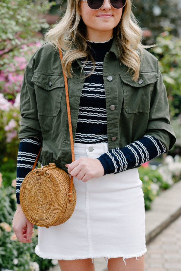 Chicago fashion blogger Bows & Sequins styling a green army jacket with a white denim skirt and a round rattan handbag.