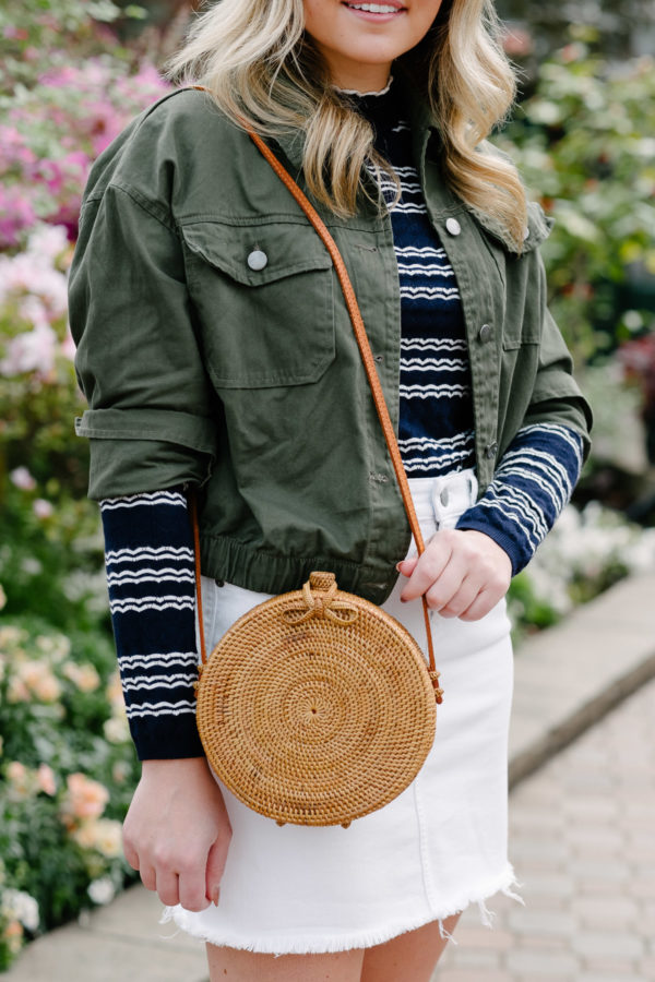 Fashion and lifestyle influence Bows & Sequins styling a round rattan Bali bag for a cute spring summer outfit with a white skirt.