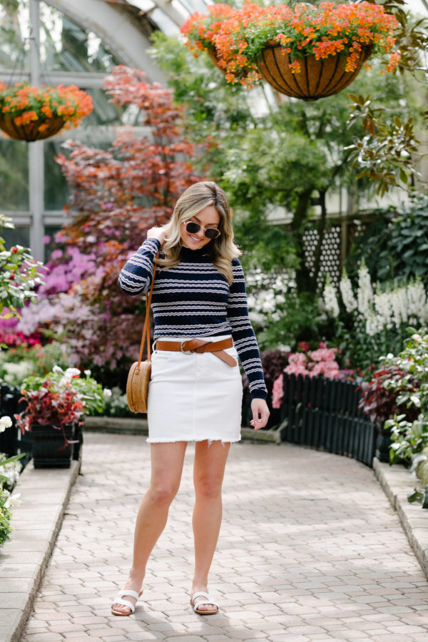 Fashion blogger Bows & Sequins wearing a striped mock neck top from Miss Selfridges with a white denim skirt and white braided sandals.
