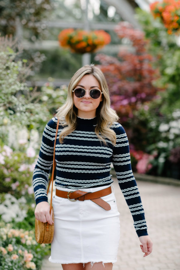 Fashion beauty and lifestyle influencer Bows & Sequins wearing a striped pointelle top with a white skirt and a knotted leather belt.