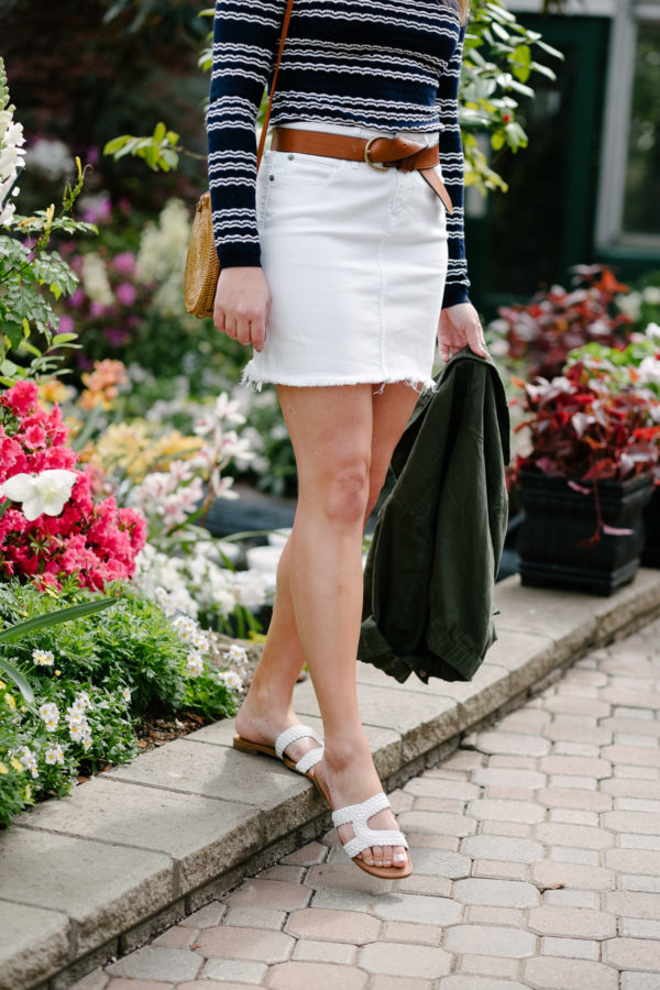 Fashion blogger Bows & Sequins styling a pair of Sam Edelman sandals with a white denim skirt.