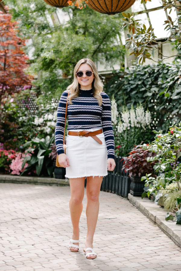 Chicago fashion blogger Bows & Sequins styling a striped top with a leather belt and white denim for a cute spring outfit.