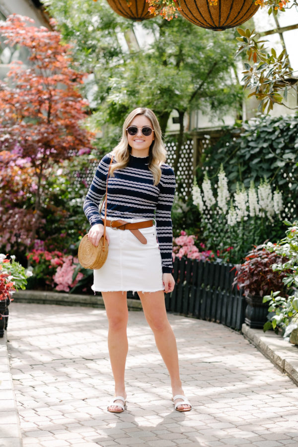 Chicago influencer Jessica Sturdy styling a cute spring summer outfit with a striped mock-neck top, leather belt, white denim, wicker bag, and braided sandals.