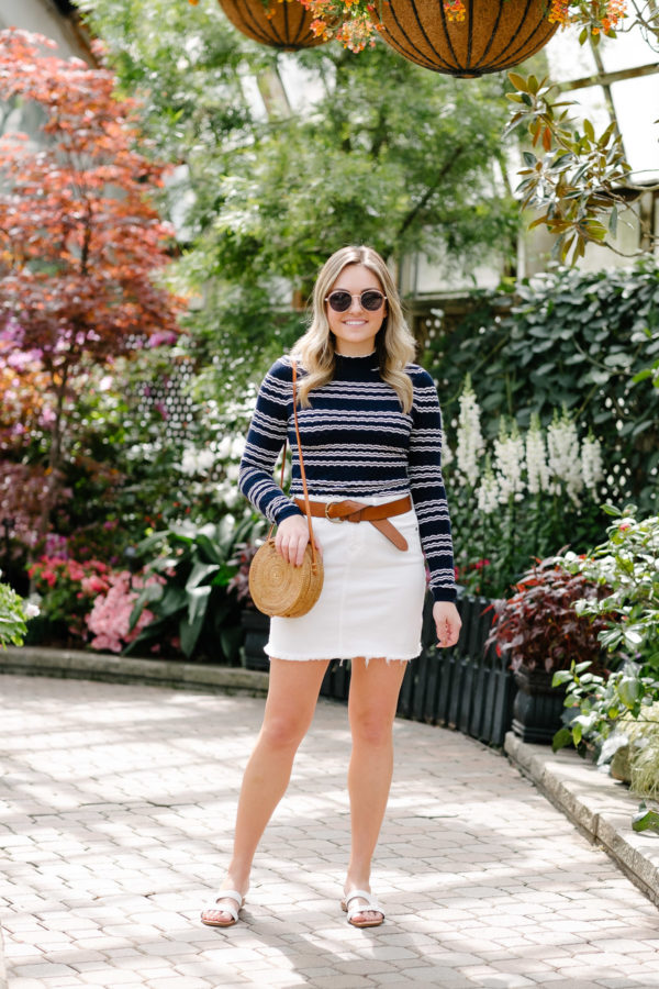 Fashion blogger Jessica Sturdy wearing a striped mock-neck top with a white skirt and a leather belt for a casual spring summer outfit.