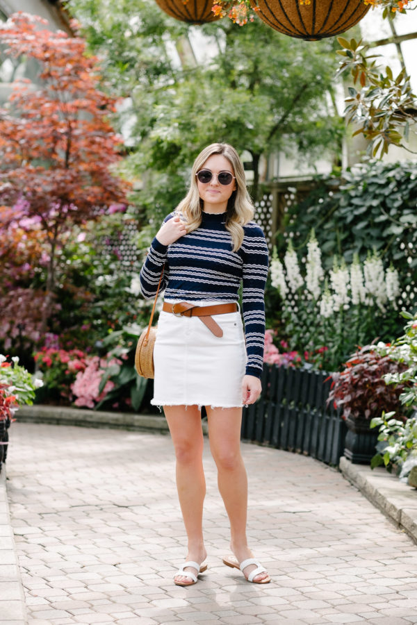 Chicago blogger influencer Bows & Sequins wearing a spring outfit with a long sleeve striped top, denim skirt, twisted leather belt, and Sam Edelman flat sandals.