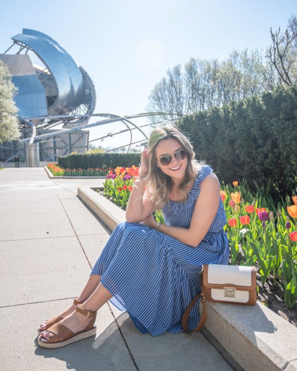 Chicago lifestyle Instagram Jessica Sturdy of Bows & Sequins wearing a blue and white striped dress with leather sandals and a canvas bag in front of tulips in Millennium Park.