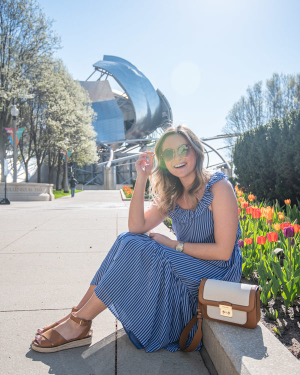 Fun Chicago blogger Bows & Sequins styling a striped midi dress with leather accessories for a cute spring outfit in front of colorful tulips in Millennium Park.