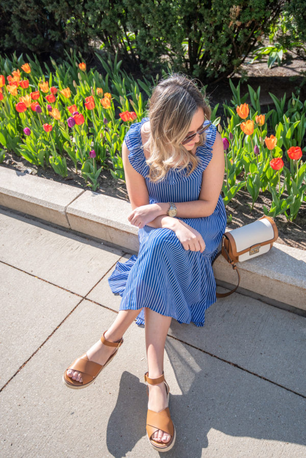Fashion focused lifestyle blogger Bows & Sequins styling a blue midi dress in front of colorful tulips.