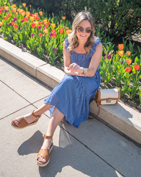 Fashion and beauty blogger Bows & Sequins wearing a blue midi dress with leather accessories and brown aviators in front of bright tulips in Millennium Park in Chicago.